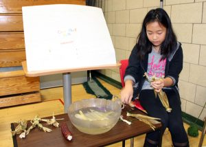 Sara Bishop, an intermediate student at Quest Elementary School in Hilton, makes corn husk dolls during Quest Feast.