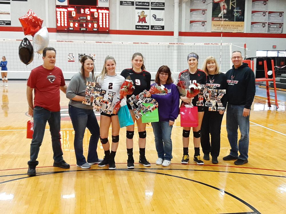 Roberts Wesleyan senior volleyball players Rachel Holmes (#2), Anastasia Smith (#9), and Kathryn Krchniak (#10) and their families on Senior Day. Photo by Warren Kozireski