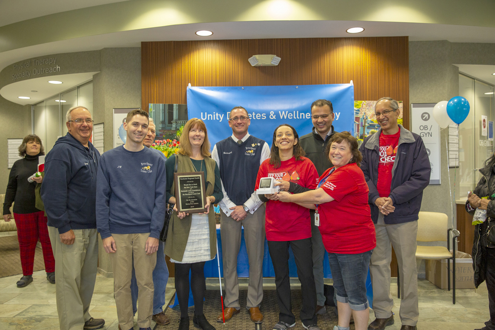 Rochester Regional Health employees presented the Brockport Lions Club with a plaque in recognition of their funding assistance in the purchase of a RetinaVue camera.