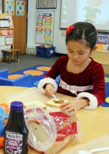 Ava Tran carefully prepares a peanut butter and jelly sandwich for the Open Door Mission.