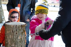 Visitors get hands-on experience with tools of maple collecting. Photo by Melody Burri