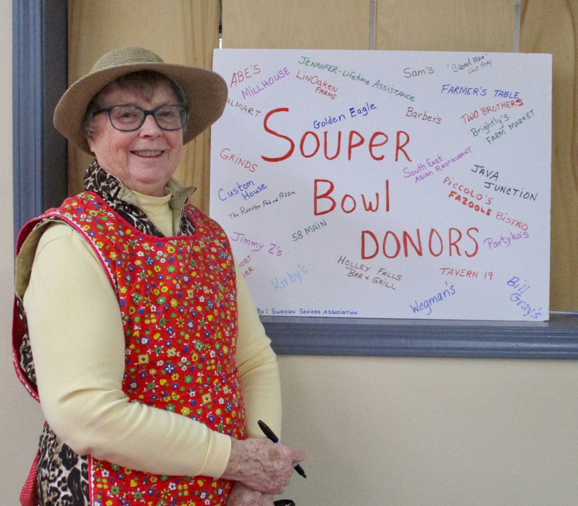 Andrea Perry, Chair of Souper Bowl III, in front of a poster naming the various restaurants that donated soup.