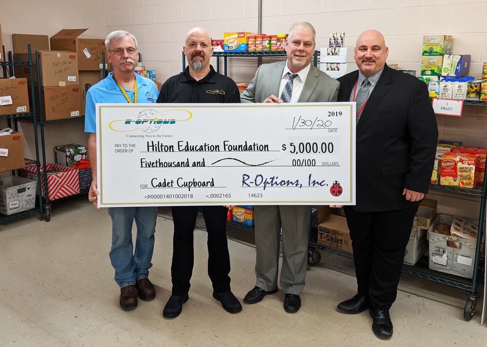 Tim Gagnon (left), Hilton Education Foundation treasurer, and Scott Ziobrowski (right), Hilton Food Service director, accept a donation from Patrick Cross, R-Options Sales and Marketing representative, and Randy DeVos, R-Options president, for the Cadet Cupboard.