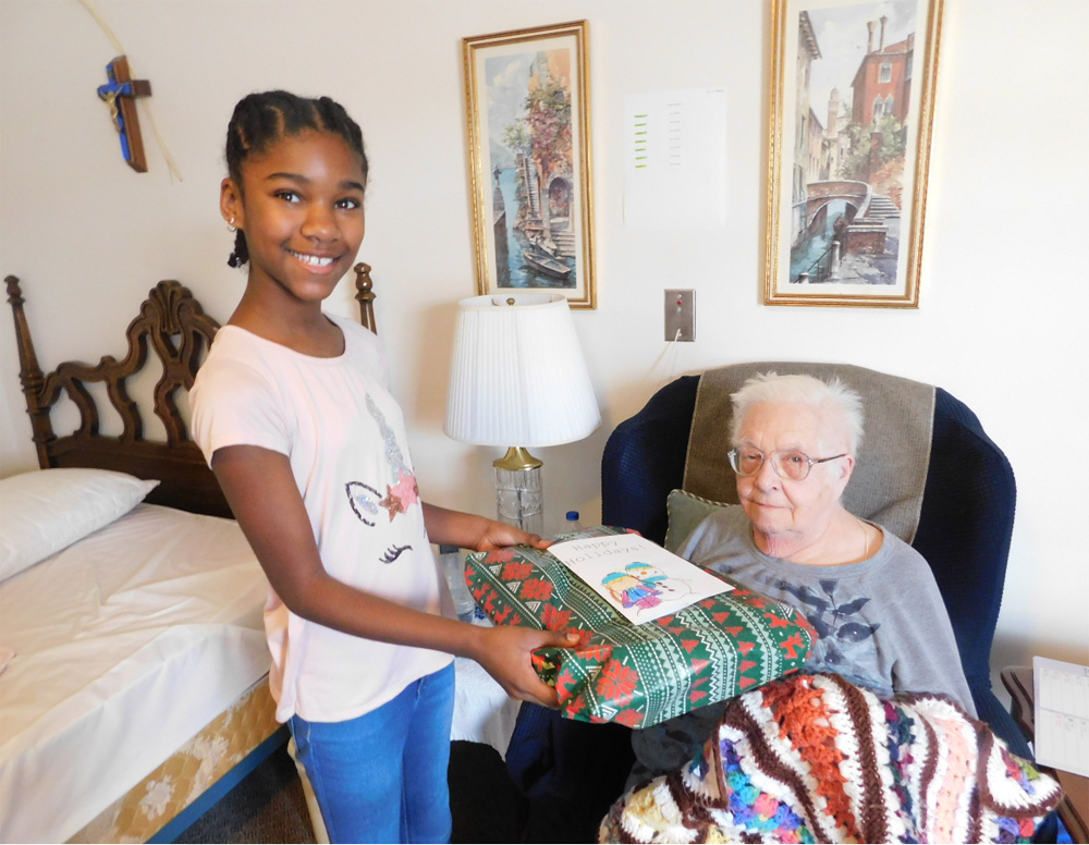 Westwood Commons resident Louise Tantalo accepts a blanket from Alaina Moldanado.