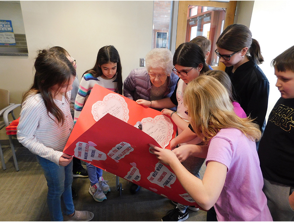 Fairbanks Elementary School students pore over the giant Valentine's Day thank you card from Westwood Commons along with resident Mary Ann Comstock.