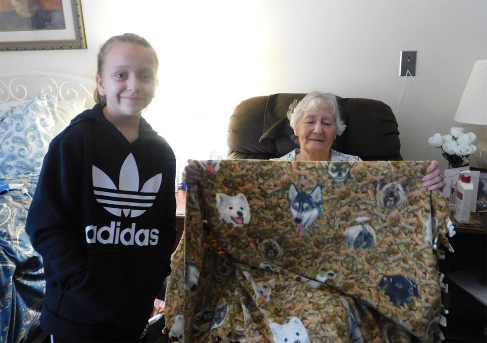 Tina L'abate unfolds the blanket she received from Fairbanks Road Elementary School student Liliana Negron.